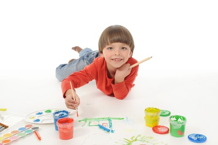 little happy boy draws paint. Isolated on white background photo