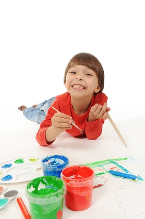 little smiling boy draws paint. Isolated on white background photo