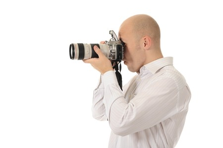 man holds a camera in his hands. Isolated on white background photo