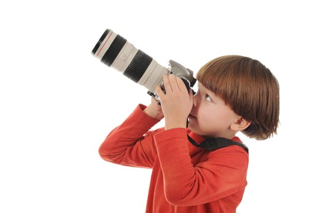 small boy holds a big camera in his hands. Isolated on white background photo