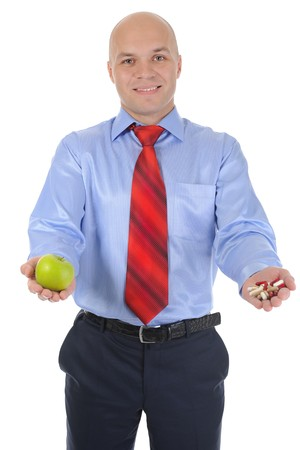 Apple and pills in the hands of a businessman. Isolated on white background photo