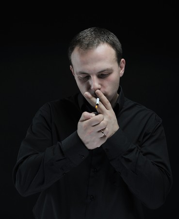 young man smokes a cigarette on a dark background Stock Photo - 8181850