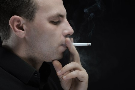 young man smokes a cigarette on a dark background Stock Photo - 8181875
