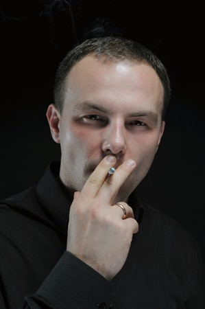 man smokes a cigarette in a dark background photo