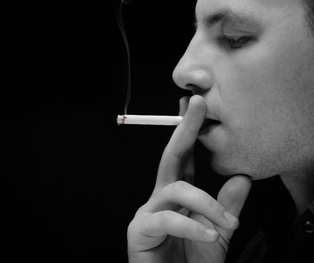 young man smokes a cigarette photo