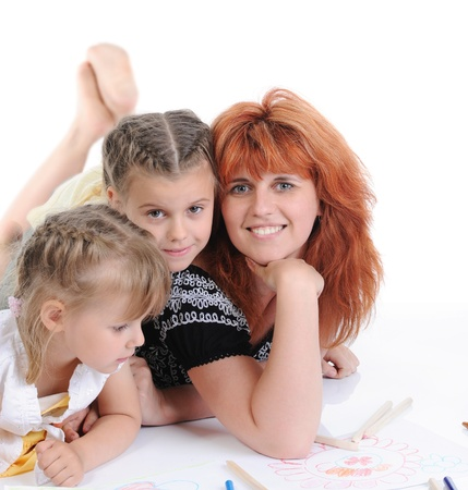 mother with her daughters draw on the album. Isolated on white background Stock Photo - 8260559