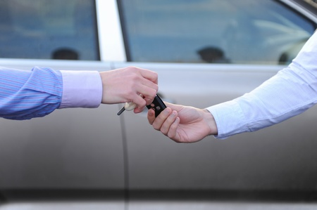 man hands the keys to the car photo
