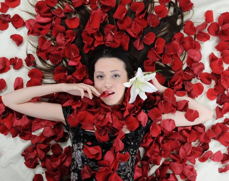 Portrait of beautiful brunette in rose petals photo