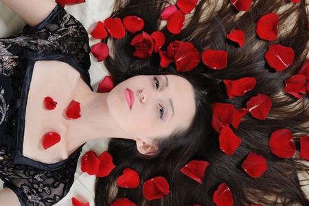 Portrait of young brunette woman in red rose petals photo