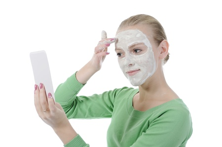young woman making a spa mask on your face. Isolated on white background photo