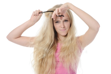 young woman with backcombing hair and scissors. Isolated on white background photo