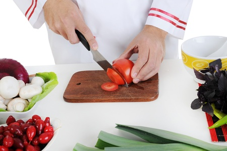 Chef in uniform cuts the vegetables. Isolated on white background photo