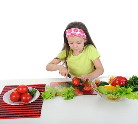 little girl cut fresh tomatoes. Isolated on white background photo