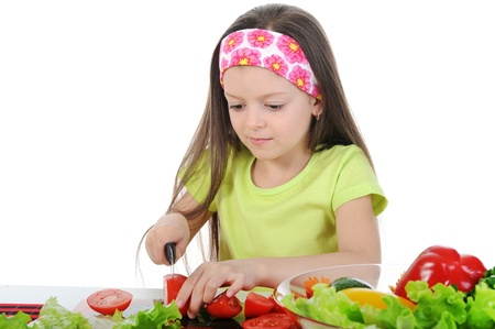 little girl cut fresh tomatoes. Isolated on white background photo