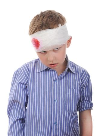 Huilende jongen met een verbonden hoofd. Geïsoleerd op witte achtergrond Stockfoto
