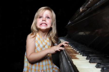 Funny girl playing on an old black piano photo