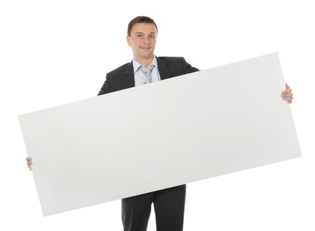 one sheet: Young smiling businessman in black suit holding large blank. Isolated on white background