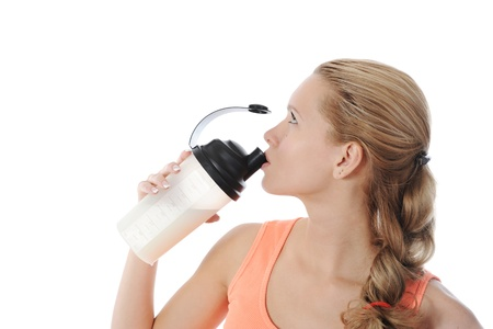 athletic young woman with protein shake bottle. Isolated on white background photo