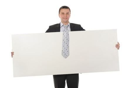 Young smiling businessman in black suit holding large blank. Isolated on white background Stock Photo - 8404304