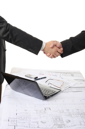 Handshake of two business partners after signing a contract. Focus on the documents Stock Photo - 8404336