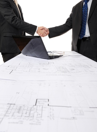 Handshake of two business partners after signing a contract. Focus on the documents photo