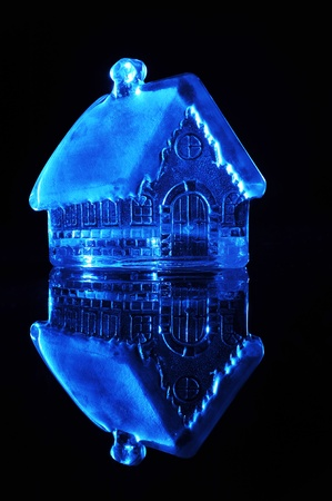Glass toy house on a black background photo