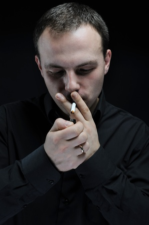 young man smokes a cigarette on a dark background photo