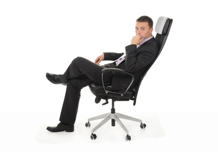 office chairs: Businessman sitting in a chair in a bright office. Isolated on white background Stock Photo