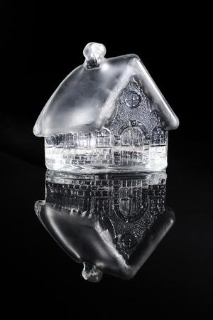 pipe dream: Casa de juguete de vidrio sobre un fondo negro Foto de archivo