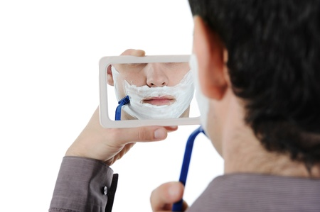 Young man shaving at the mirror. Isolated on white background photo
