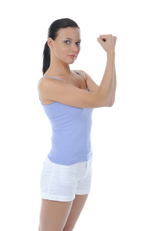 Beautiful woman athlete demonstrates muscles. Isolated on white background photo