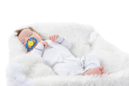 baby sleeps with a pacifier in her mouth. Isolated on white background photo