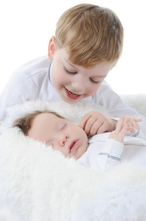 little boy looks at the sleeping brother. Isolated on white background photo