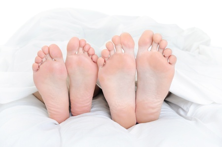 Close-up of the feet of a couple on the bed. Isolated on white background photo