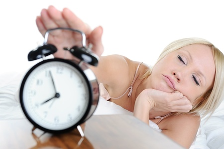Sleepy woman turns off the alarm. Isolated on white background photo