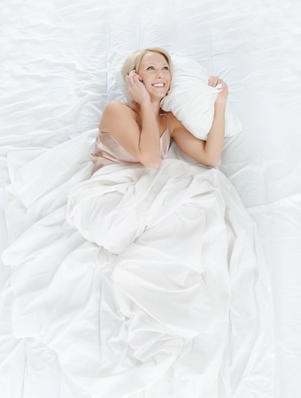 beautiful young woman talking on the phone while lying in bed Stock Photo - 8596789