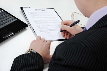 Businessman signs a contract at the table in the office photo