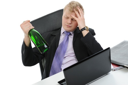 Drunk businessman drinking champagne on the job in the office. Isolated on white background photo