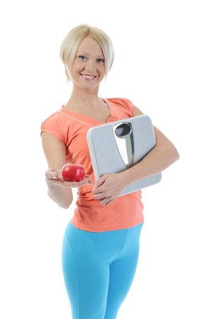 young athletic woman with an apple and scales  in the hands of. Isolated on white background Stock Photo - 8596785