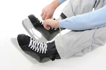 Man tying shoelaces hockey skates. Isolated on white background photo