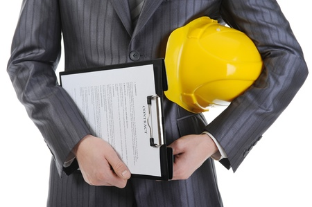 Businessman with construction helmet and clipboard . Isolated on white background photo