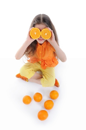 Funny girl sitting on the floor with oranges. Isolated on white background photo