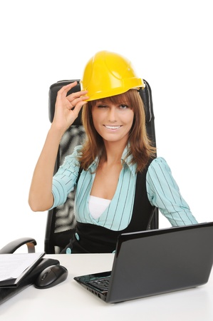 Joyful businesswoman in a helmet in the office. Isolated on white photo