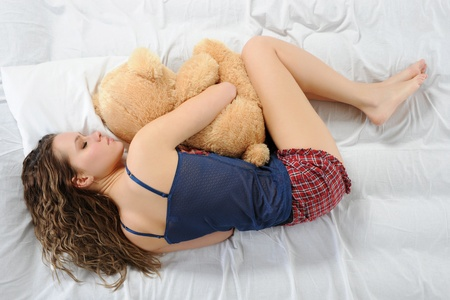 Young woman sleeping on a bed in an embrace with teddybear photo