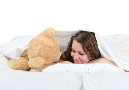 Young woman on a bed in an embrace with teddybear. Isolated on white background Stock Photo - 8734503
