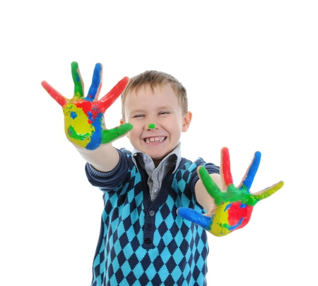 smiling boy with the palms painted by a paint. Isolated on white background photo