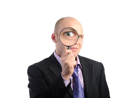 loupe: Businessman looking through a magnifying