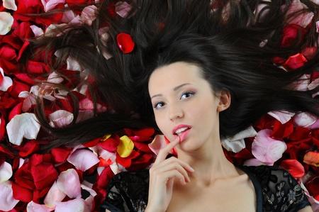 beautiful brunette in rose petals photo