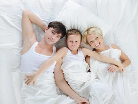 enfant qui dort: Famille heureuse gisant au lit