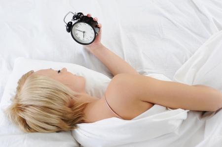 Sleepy woman turns off the alarm Stock Photo - 8735316